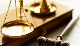 Close-up of weights balancing scales of justice with gavel beside it