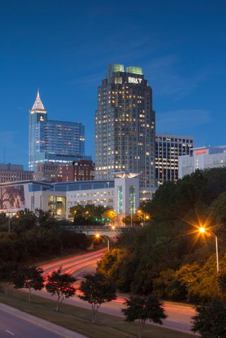 Empty road with urban skyline on background at dusk, Raleigh, North Carolina, USA