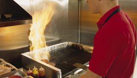 Fast food worker flips hamburgers