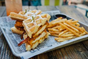 Fried Chicken and bacon waffle sandwich with french fries in an outdoor restaurant setting.